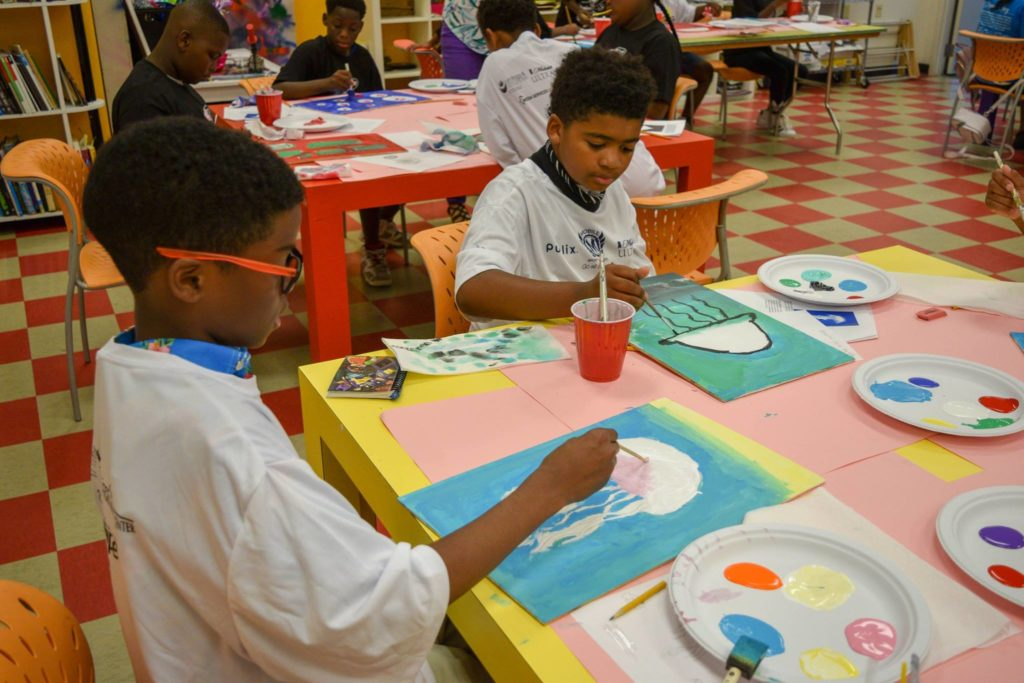 Boys & Girls Club students painting jellyfish on recycled wood canvases